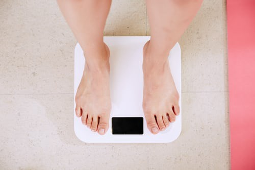 Image of a woman on a bathroom scale contemplating the 'quarantine 15' keto diet weight loss after pandemic