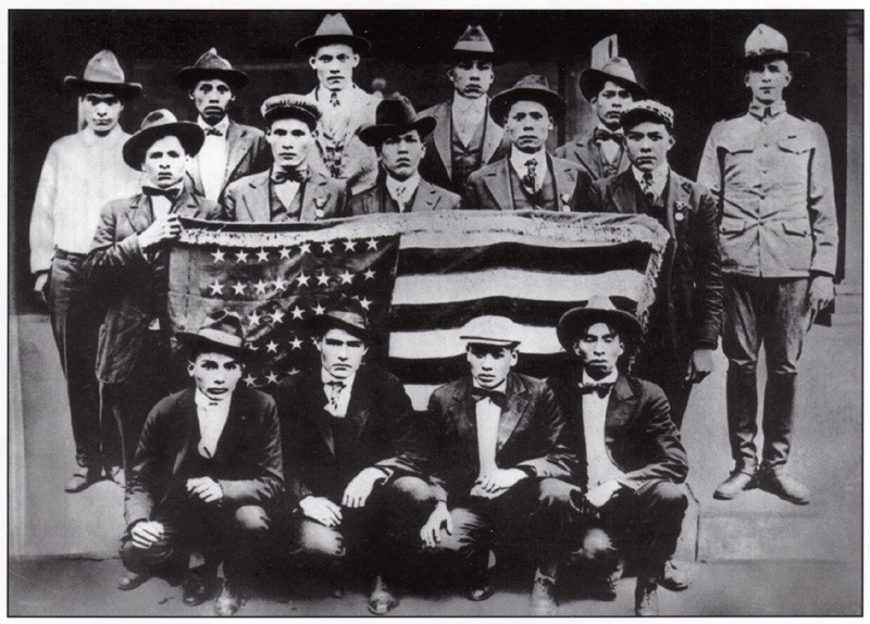 A group of men hold up an American flag