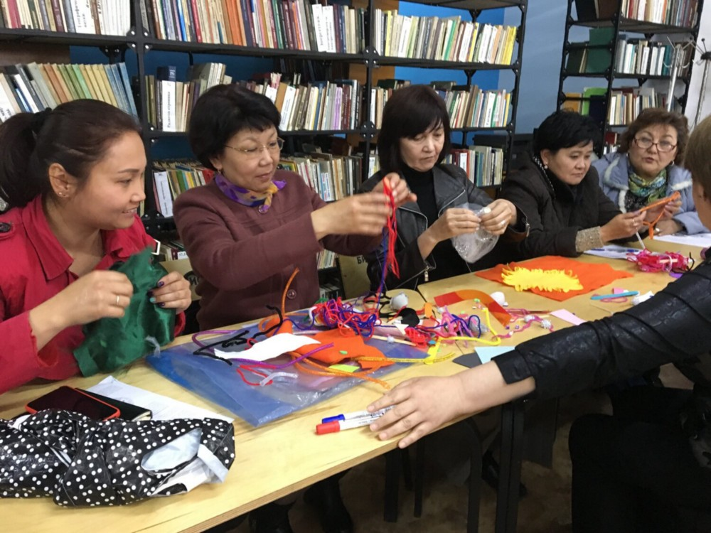 Five women are seated at a table with arts and crafts materials.