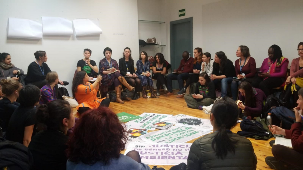 A group of people in a circle listening to speakers with rally signs in the middle of the circle on the floor