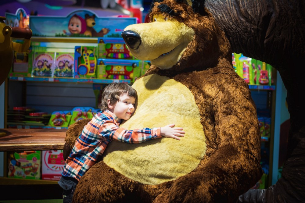Child hugging an enormous stuffed bear in a toy store.