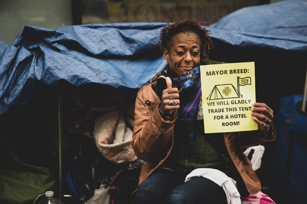 """A Black person sits in front of their tent smiling, with their thumb up next to a sign that reads """"Mayor Breed we will gladly trade this tent for a hotel room!"""""""