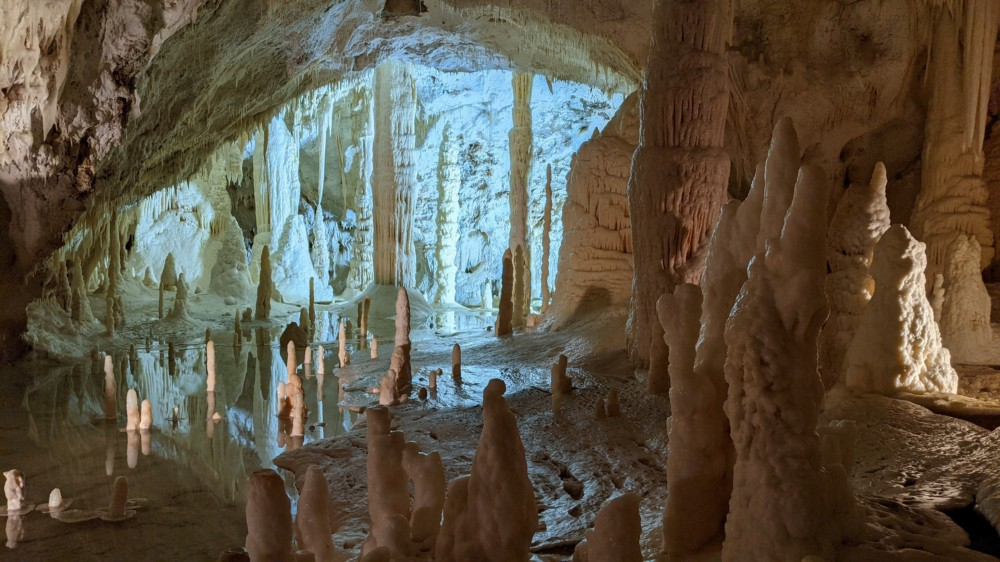 Stalactites and stalagmites in a white and blue cave.