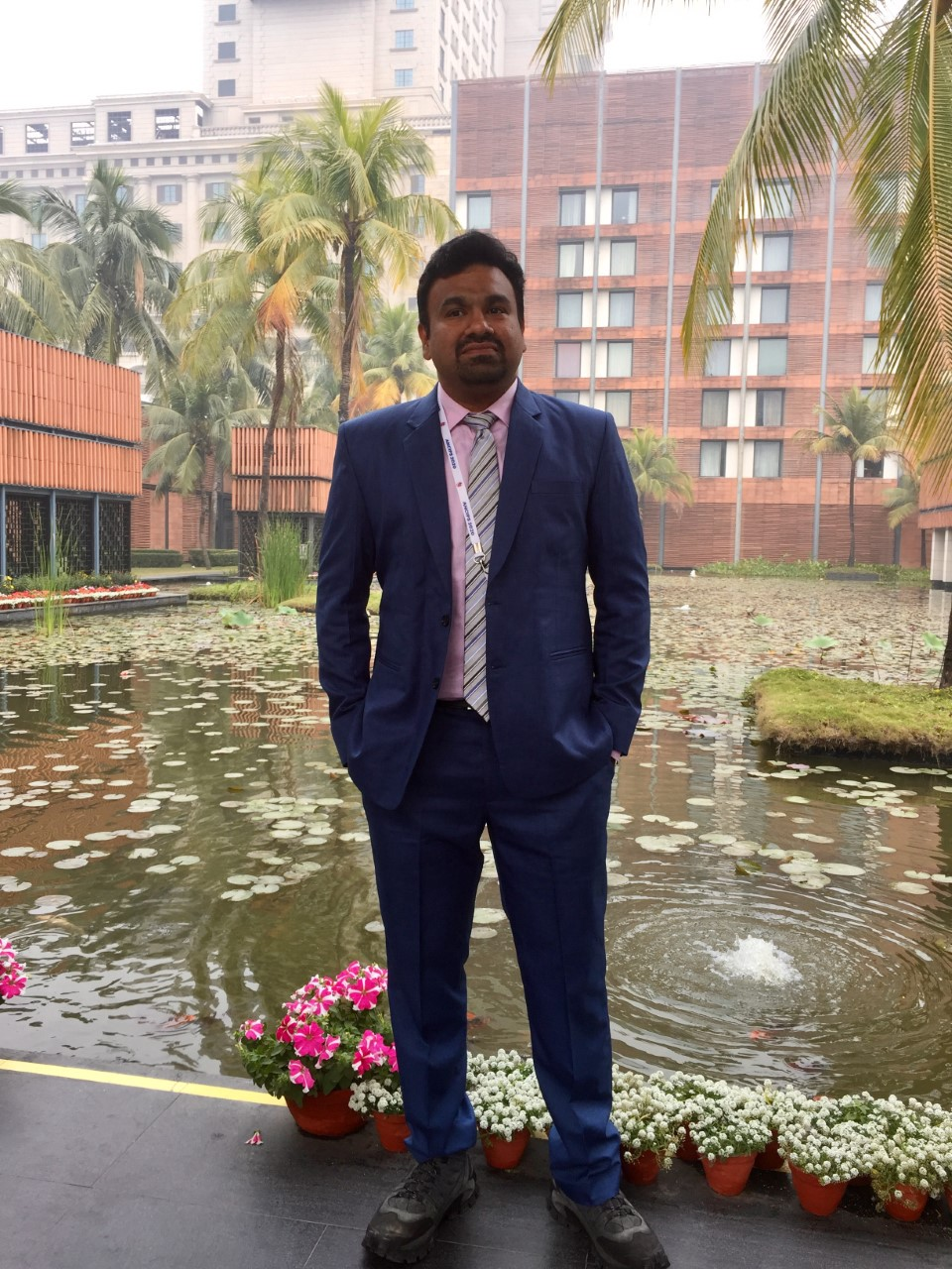 Dr. Sharad in a dark bule suit standing in front of a pool