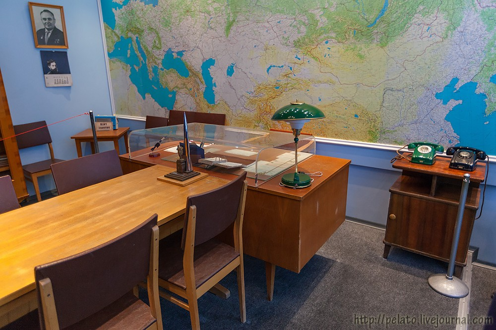 A small office with a wooden desk and table, a giant map of Russia behind it. The lamps and phones are old-fashioned and the desk's papers are covered in glass.
