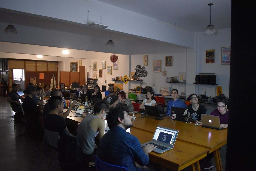Eighteen people sitting at a shared table with their computers, learning p5.js.