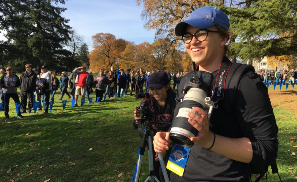 Erika Soderstrom holds camera while covering a national cross country meet in Vancouver, WA