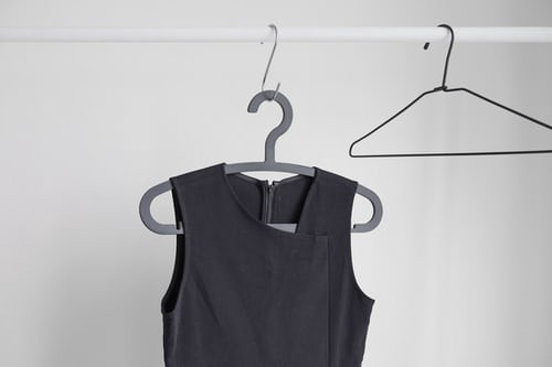 Single black sleeveless dress on a hanger. An empty hanger is to the right of the dress.