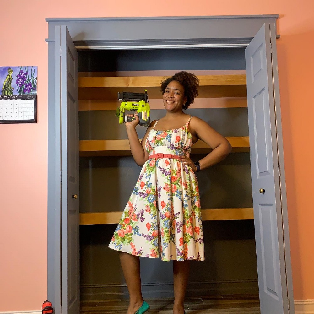 A open closet. Tamarah is standing in front wearing a white floral dress and holding a green Ryobi brad nailer. Behind her are 3 floating shelves she built. The closet wall, closet door and the trim are a blue/dark grey. The room color is pink and there is a stripe of pink in the middle top inside the closet.