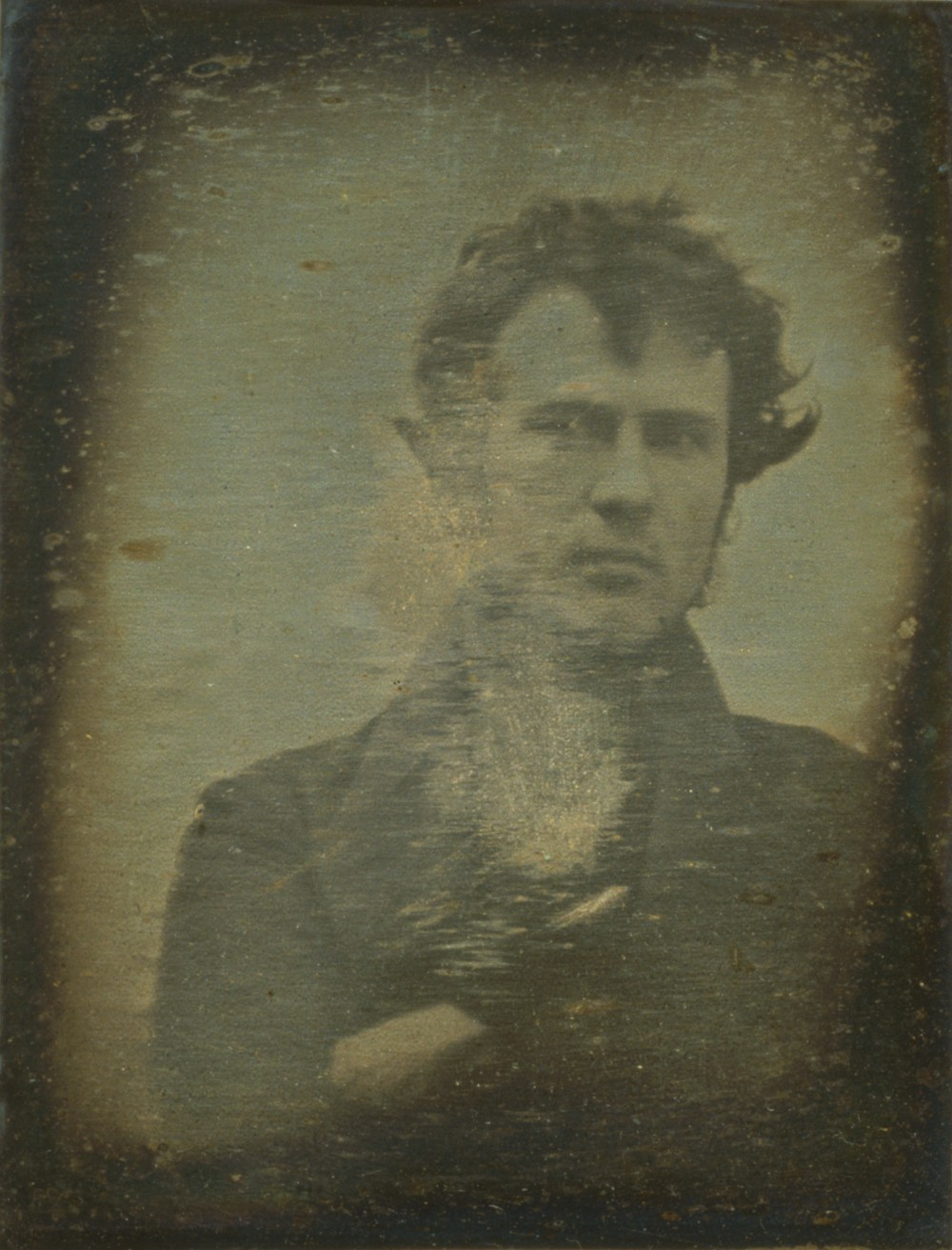 A sepia-toned photograph of a young man in a dark coat.