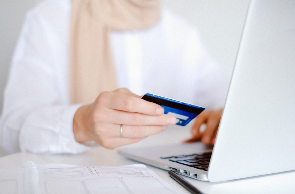 A woman holding a credit card as she looks at a laptop