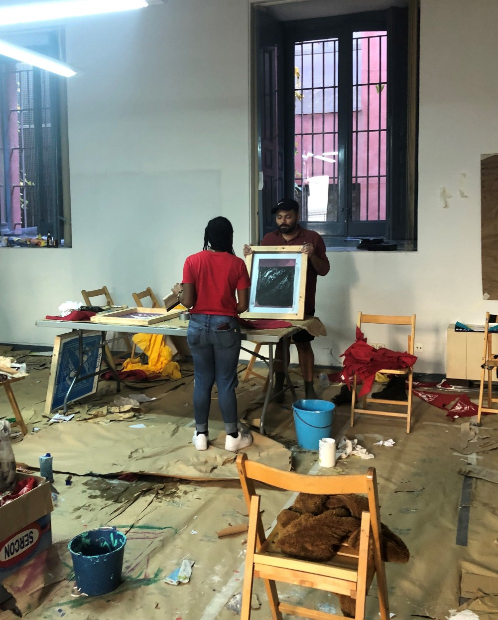 Two activists, Nyiesha and Carlos, creating protest art in a workshop
