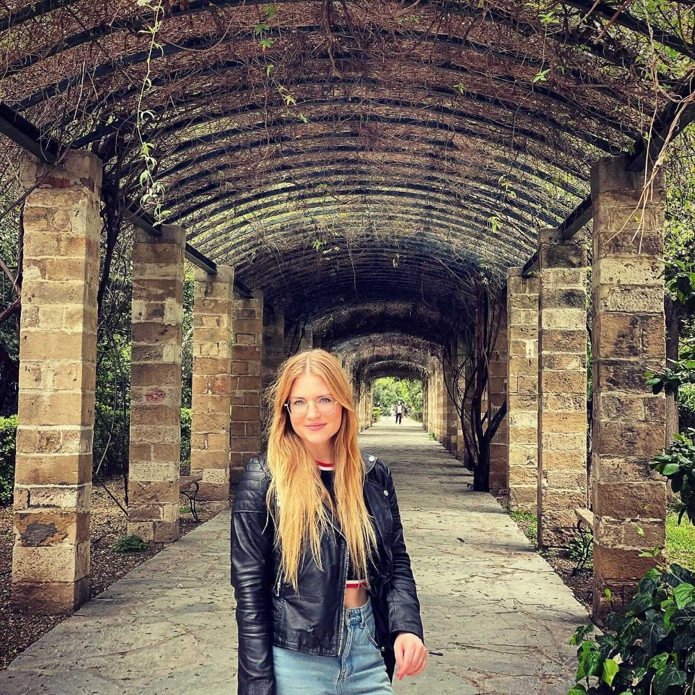 A young blonde in glasses woman standing in the center of a brick archway in Europe