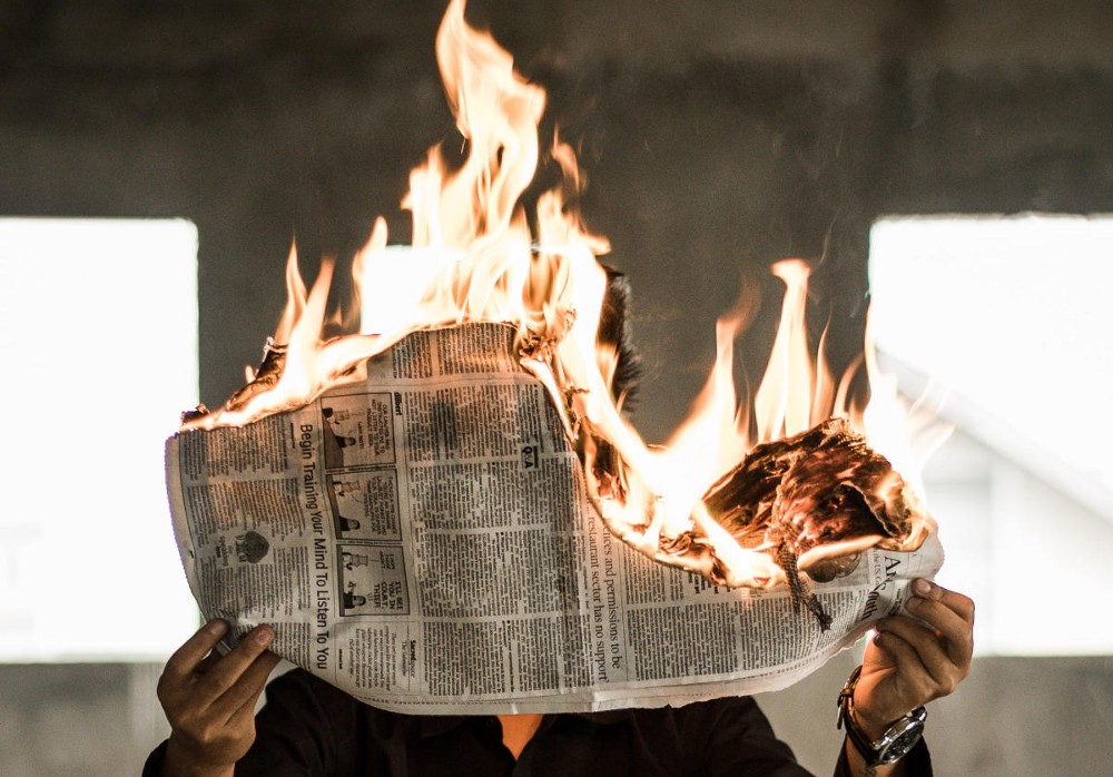 A man holds a newspaper on fire as a metaphor for the demise of news media.