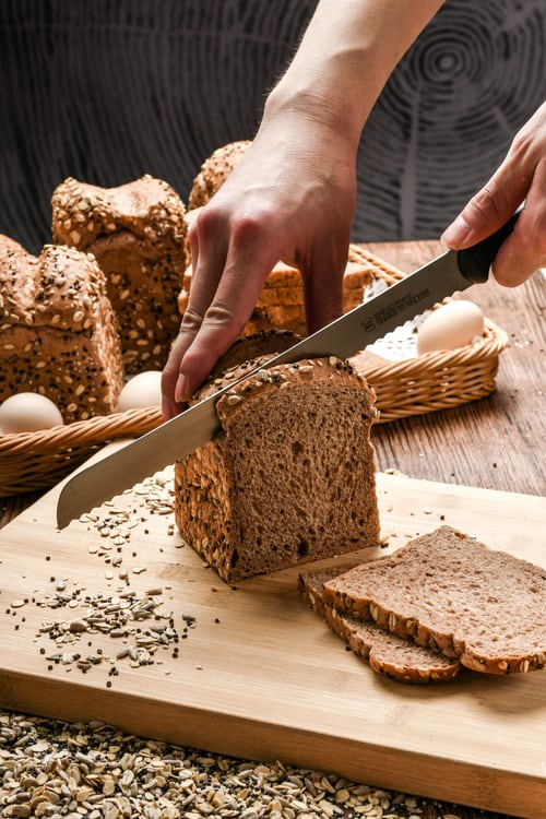 Man slicing keto bread with only 2 net carbs quarantine 15 nutrail weight loss
