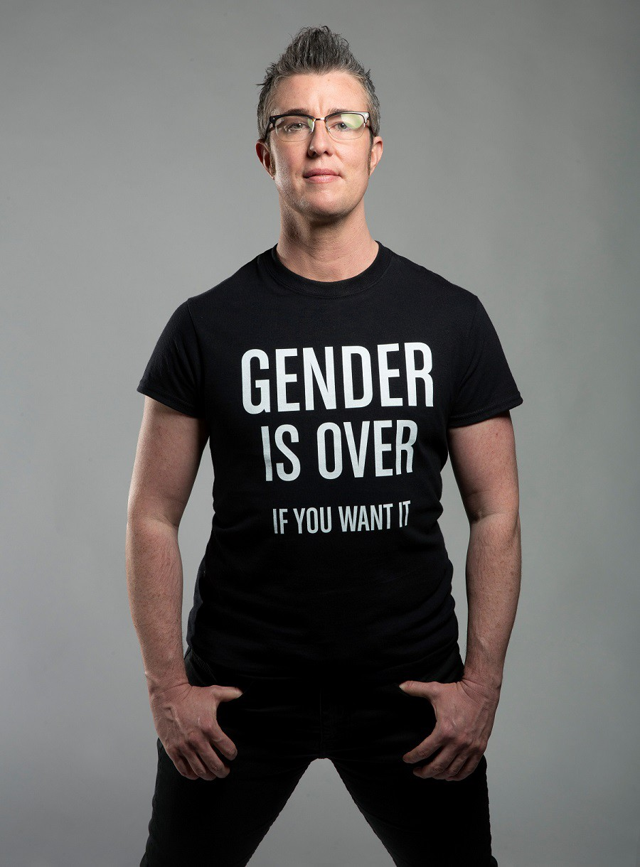 """Dorsey against light grey background wearing a black shirt with white letters that reads """"GENDER IS OVER IF YOU WANT IT"""""""