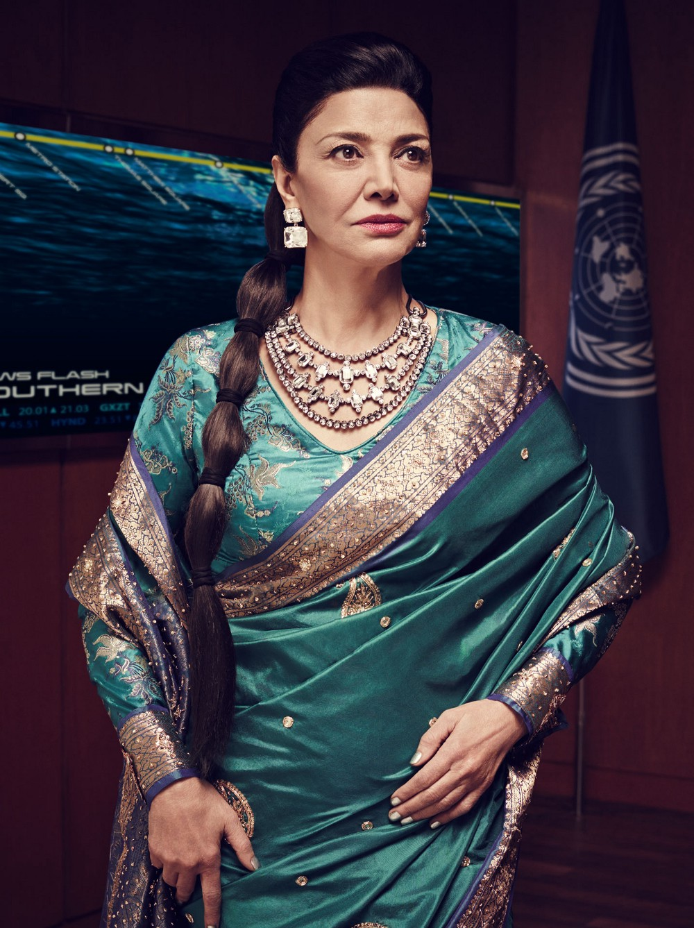 Chrisjen Avasarala from the Expanse. An older tan-skinned woman in an emerald-toned dress.