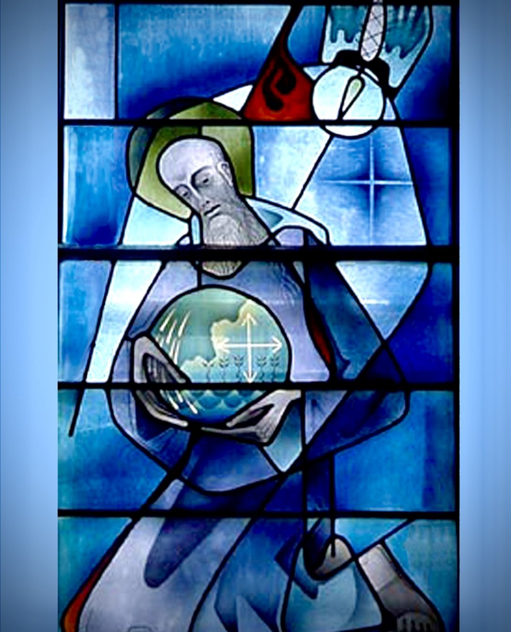 Blue color stained glass window in Mount St. Scholastica Monastery of St. Benedict holding globe of the world in his hands.