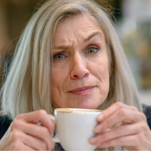 Lady frowning in disbelief whilst drinking coffee
