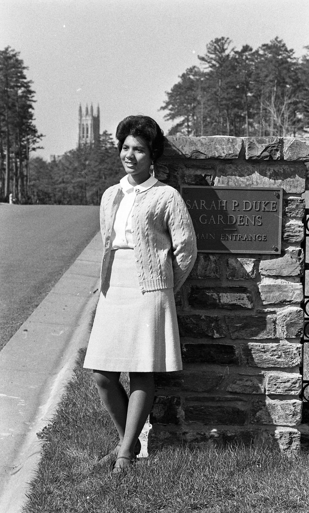 """Wilhelmina Reuben, May Queen 1967, leans on a stone column with a plaque that says, """"Sarah P. Duke Gardens, Main Entrance."""""""