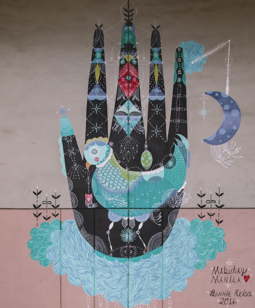 Elaborately decorated painting of. hand on a wall, with a moon to the right