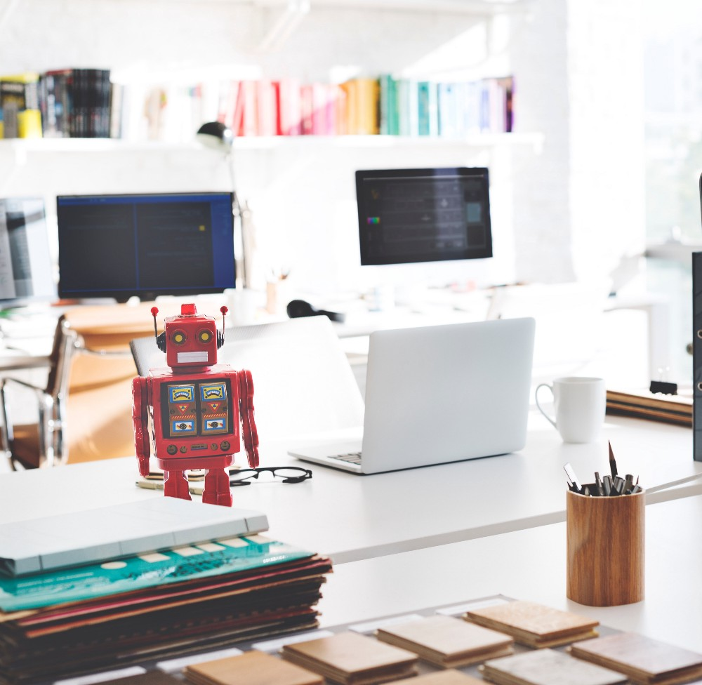 Robot on desk with computer monitors