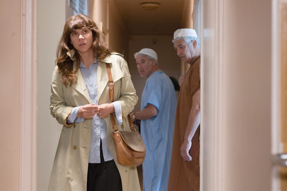 A woman walks down a hallway, two men look in her direction.