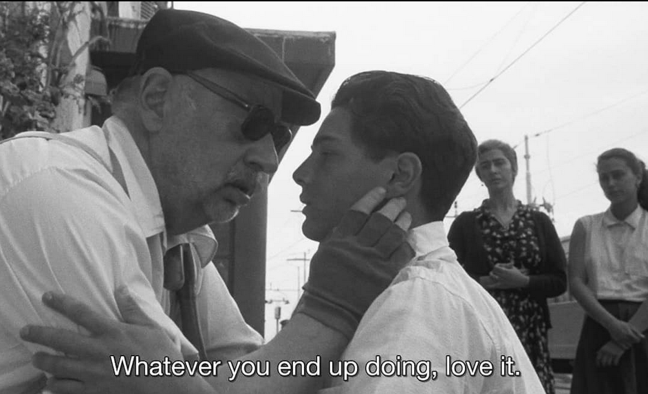 Black and white screenshot from the film: Cinema Paradiso directed by Giuseppe Tornatore. An older man holds a young boy's face. The subtitle reads: whatever you end up doing, love it.