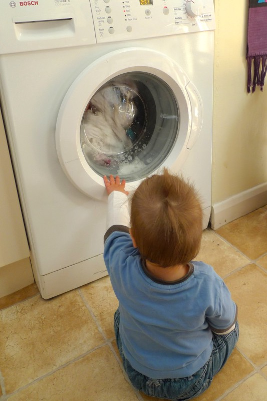 A young child sitting in front of, and touching a washing machine
