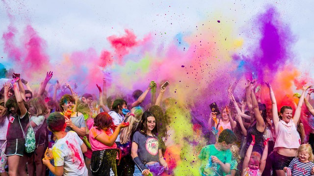 Multi-colored clouds of powder float in the air above heads of several people being coated in the colors. Many of the people have their arms raised in the air.