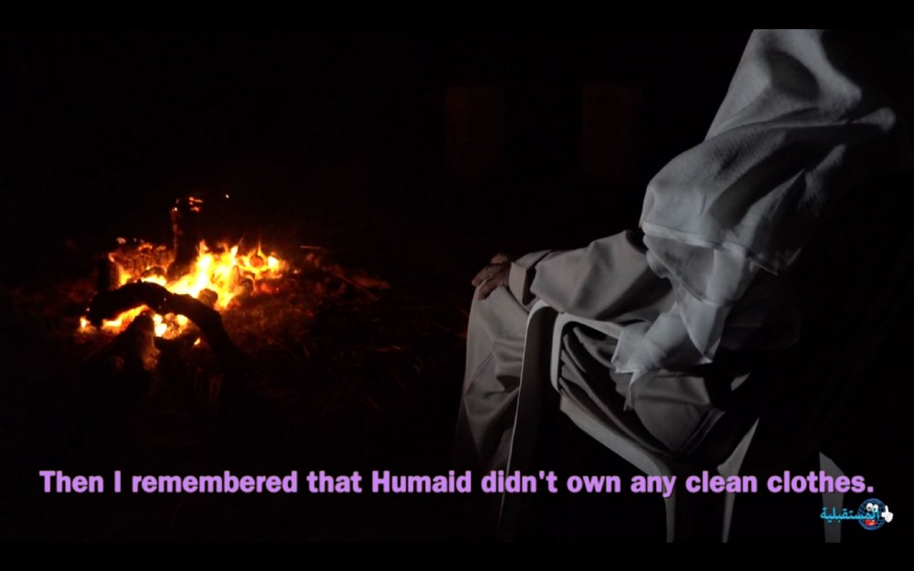 A man in traditional clothing sits by a bonfire telling the story of his encounter with a jinn.