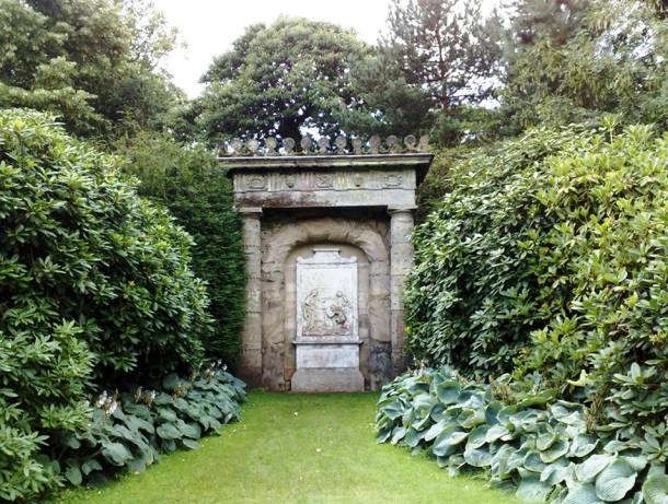 A grassy path between lush shrubbery and trees leads to a stone sculpture with ornate carvings and inscriptions.