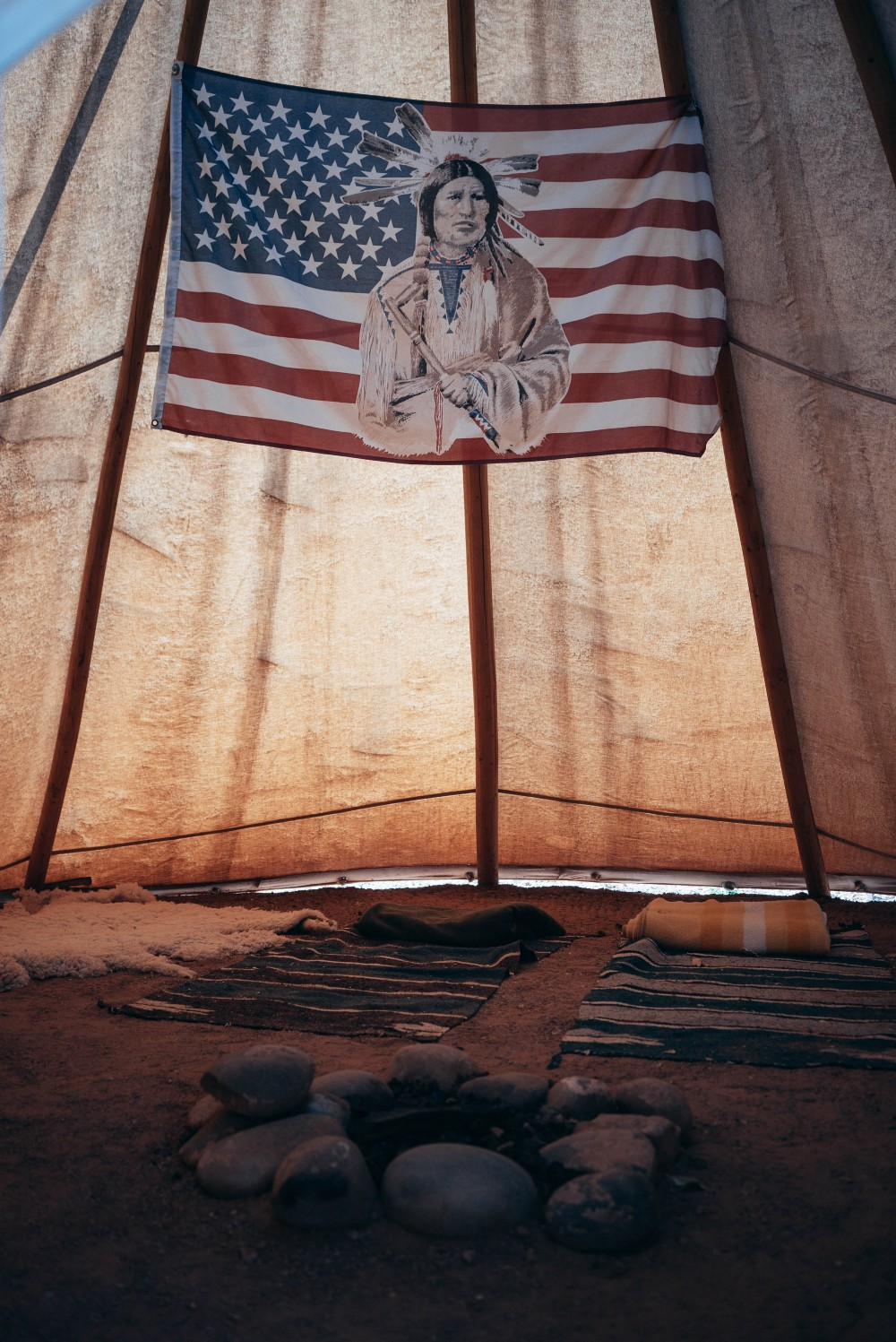 An image of a Native American elder imposed in the middle of an United States flag hangs from the inside of a tent styled in the tradition of an Indigenous tribe, complete with fur pelts, blankets, and a stone bordered fire pit on the earth beneath.