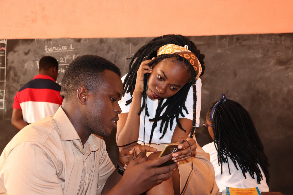 Students in a classroom using mobile phone technology.