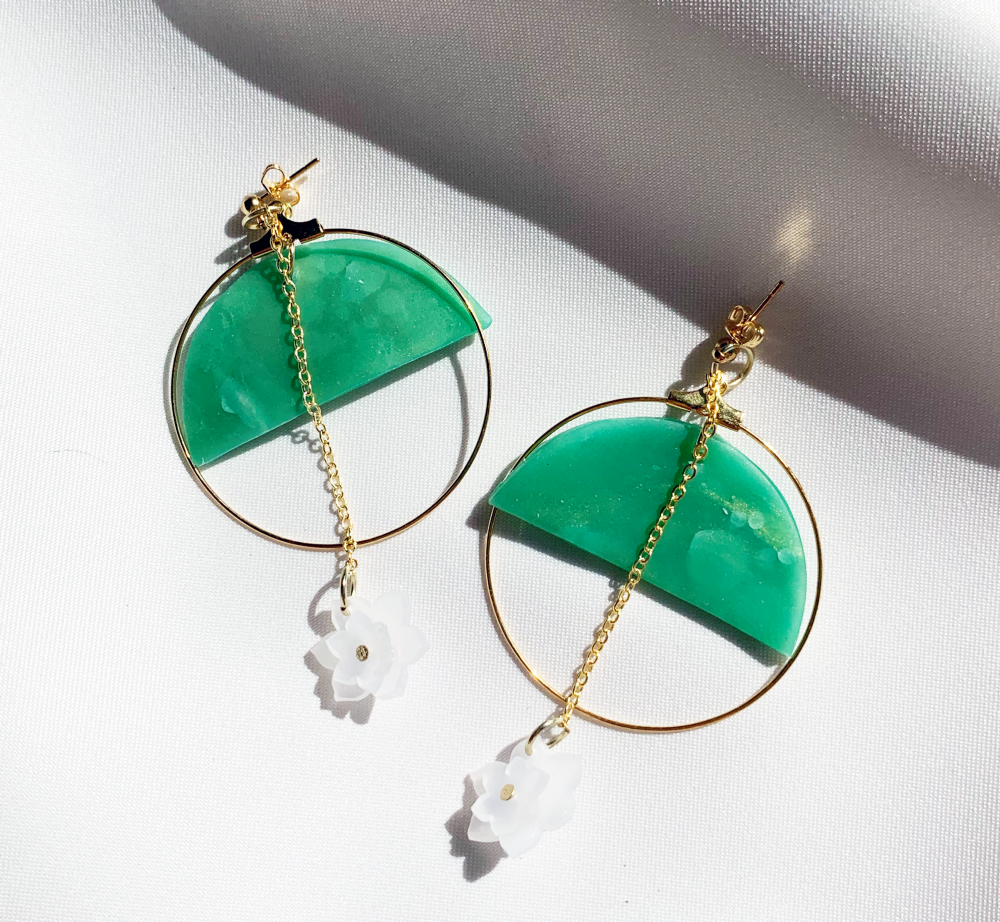 Circular earrings with a jade semicircle and a white flower on a chain that runs down the middle