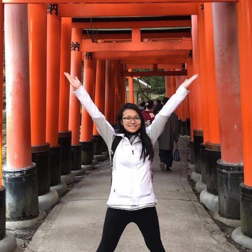 Tiffany standing with her arms up in front of a tunnel made up of red gates.
