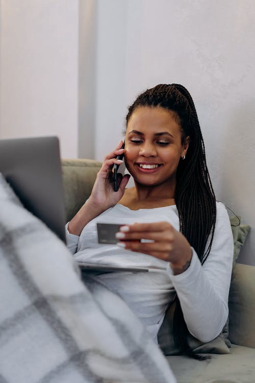 Picture of a woman on the phone holding a credit card in her hand.