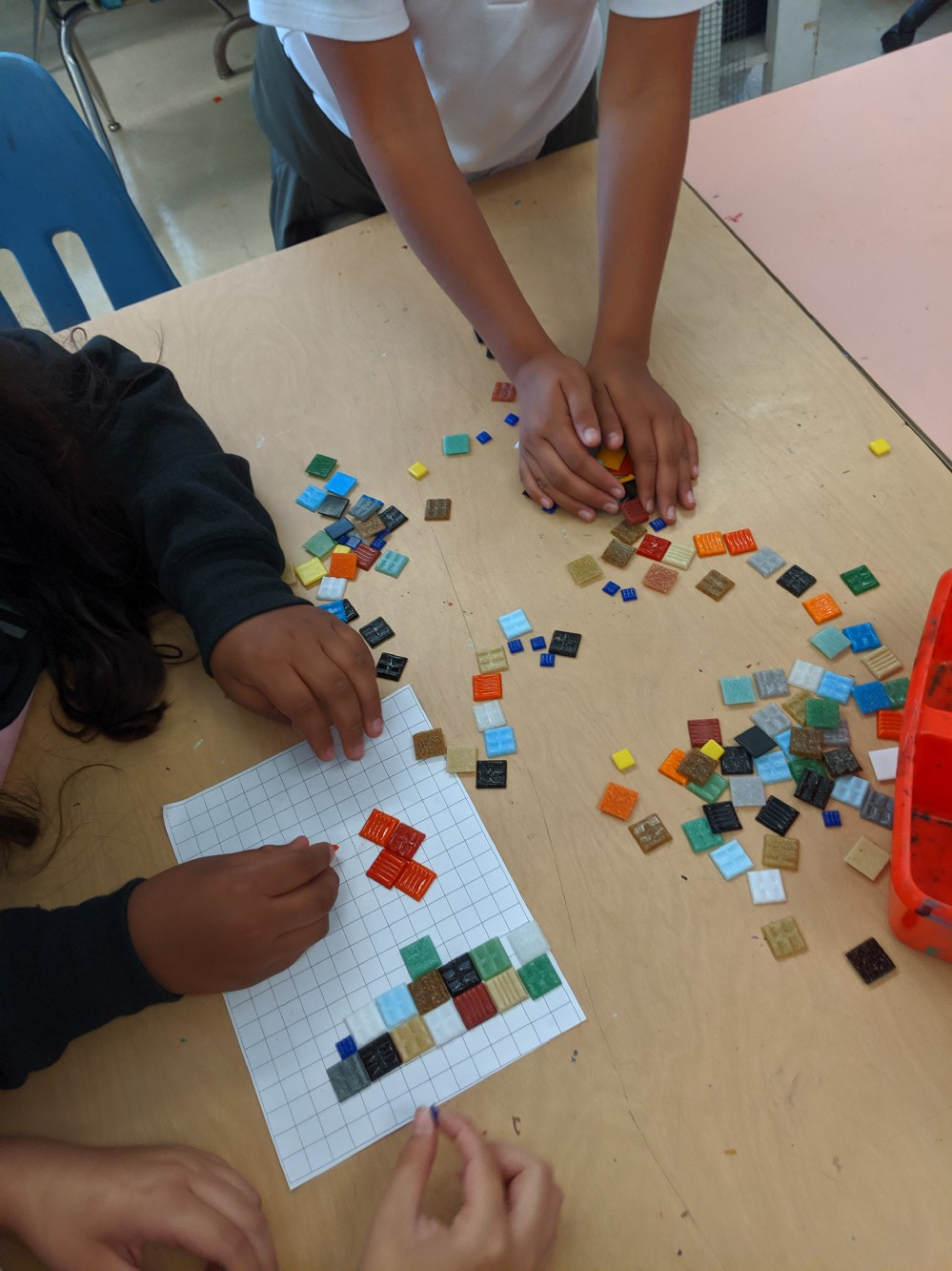 Three students working with mosaic tiles. They are laying them on grid paper to create a picture.