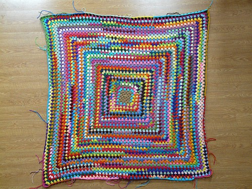 A very large granny square made from yarn scraps