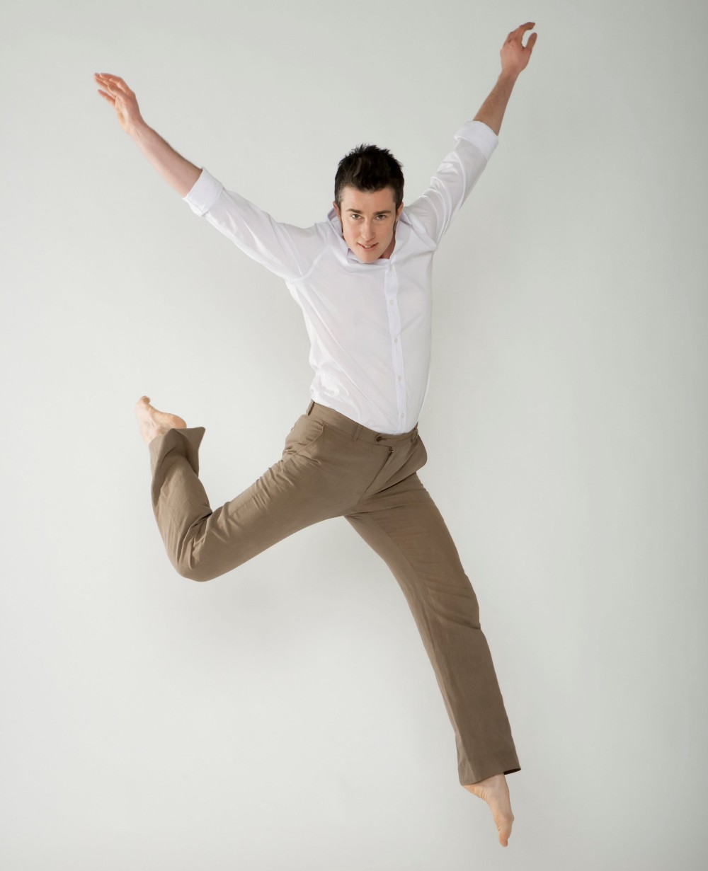 Dorsey in white shirt and tan pants, jumping in the air, back knee bent, both arms raised