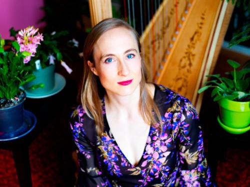Composer Hannah Lash in purple floral shirt sitting in front of a harp and assorted potted plants