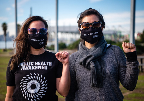 Photograph of two Public Health Awakened members in Public Health Awakened gear holding up their fists in solidarity.