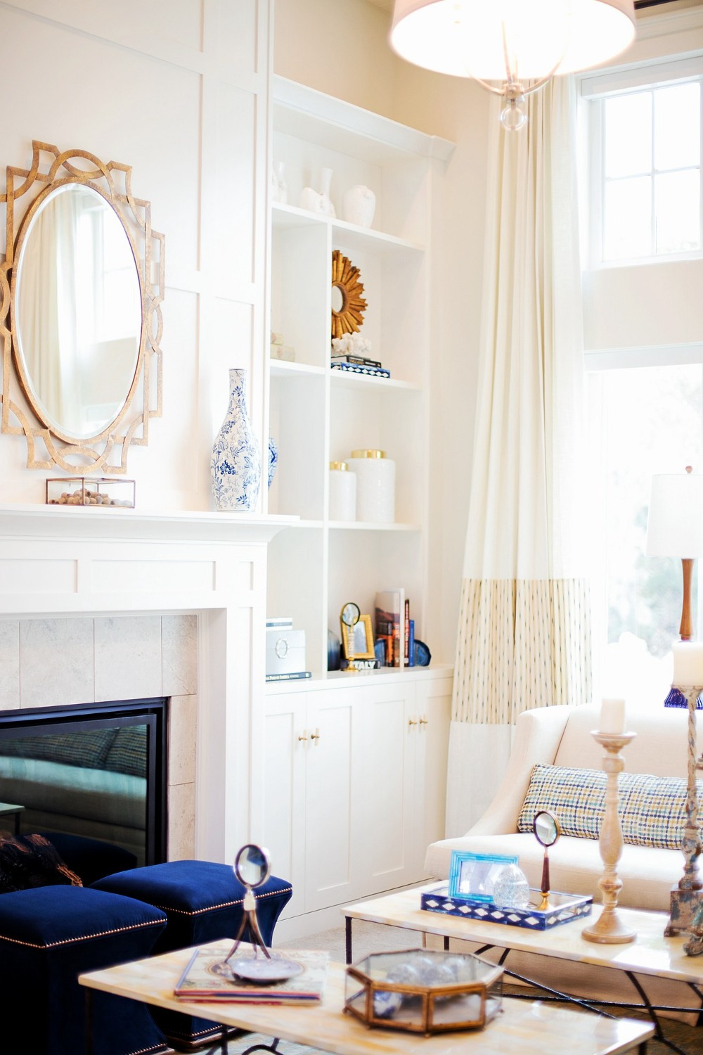 Bright and cheerful living room with white walls and cabinetry and blue and gold decor.