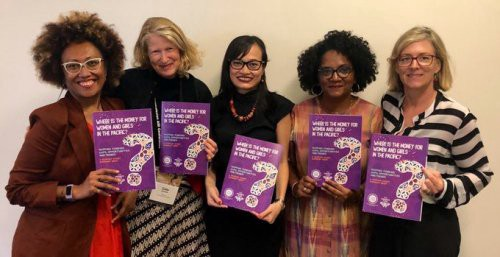 Five female figures smiling and looking at the camera while holding up purple-coloured copies of a report.