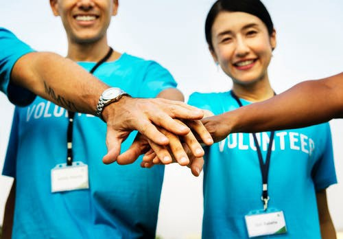 A group of volunteers with their hands stack on top of each other