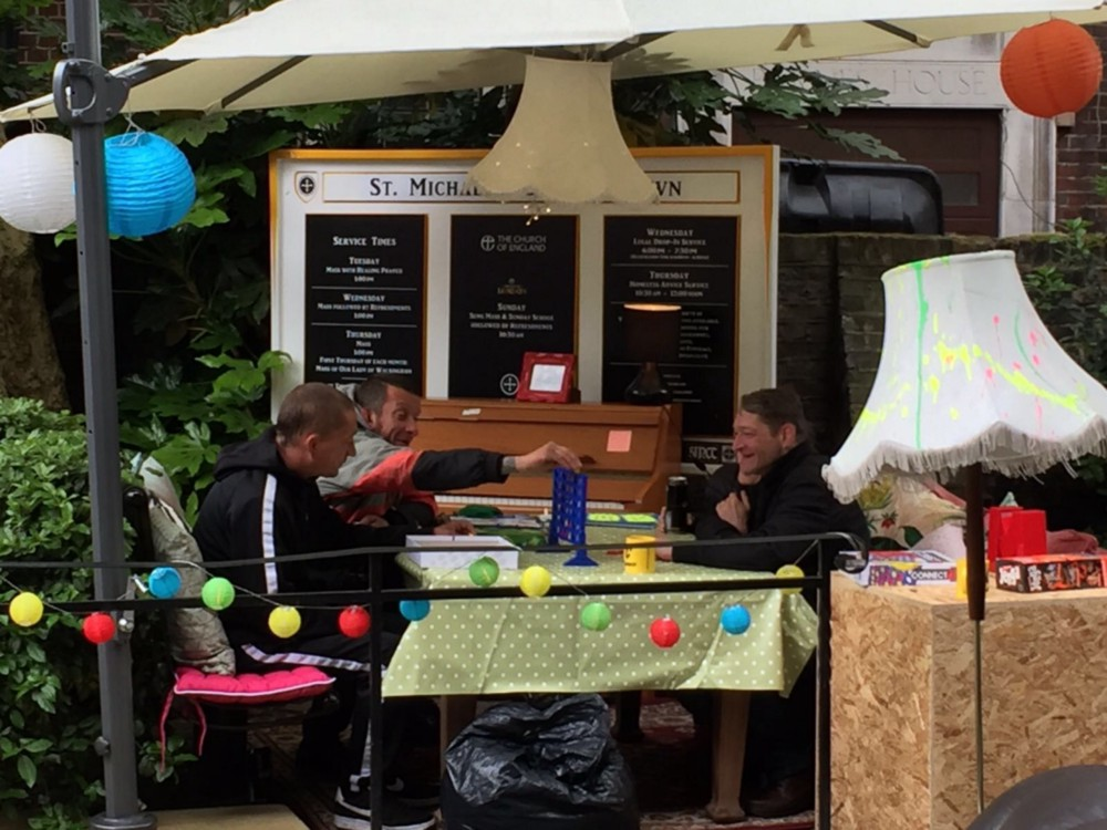 Three men are sat at a table playing connect 4.