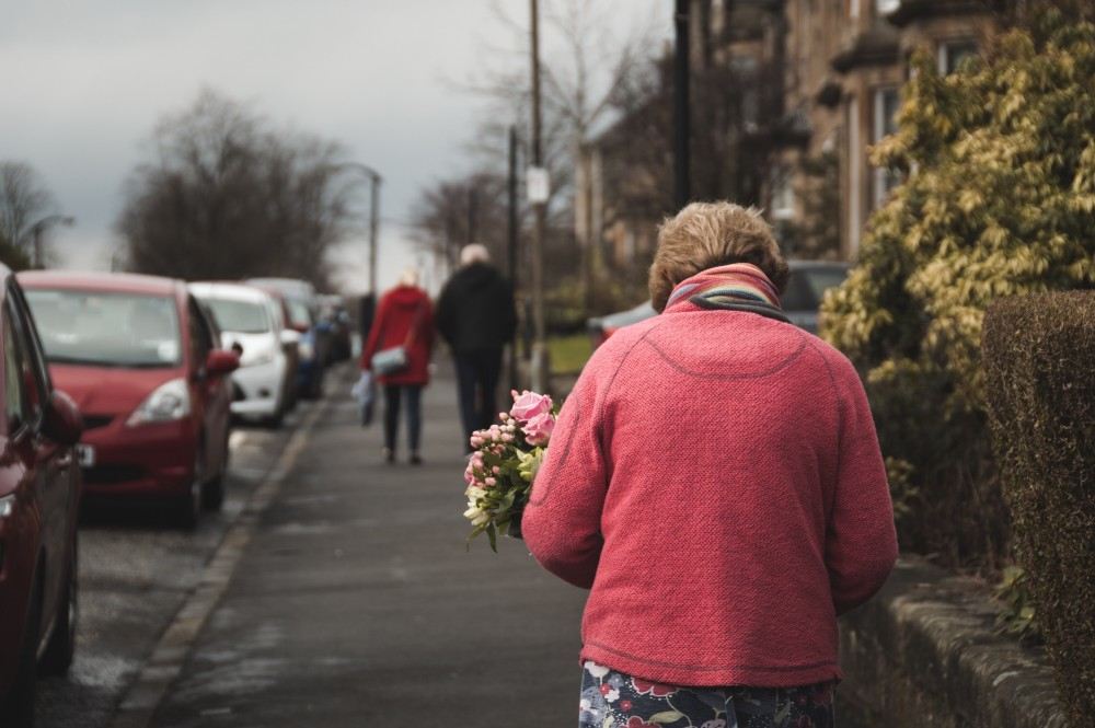elderly woman carrying a bouquet of flowers while walking down the street