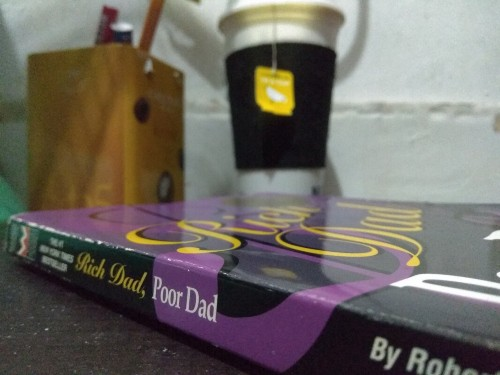 Rich Dad Poor Dad book on a table with a cup of tea.