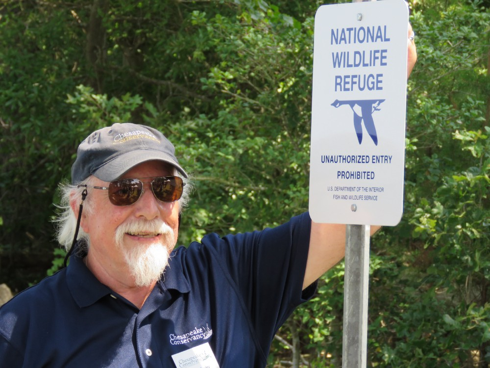 Man in baseball hat and glasses standing next to a sign that reads National Wildlife Refuge Boundary