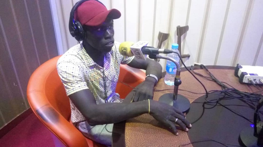 Seme Lado in a radio station talking to a microphone. He is wearing a white checkered shirt and a red hat.